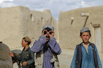 An Afghan resident reacts to the cameras as others look on, during a patrol by U.S. soldiers from 3/1 AD Task Force Bulldog, in a village at Kherwar district in Logar province