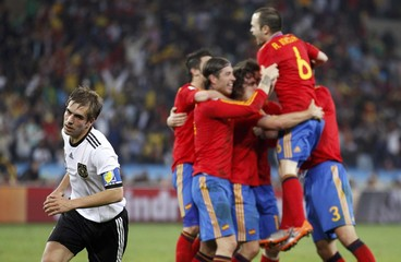 Germany's Philipp Lahm reacts on the pitch as Spain's players celebrate near him after a goal in Durban