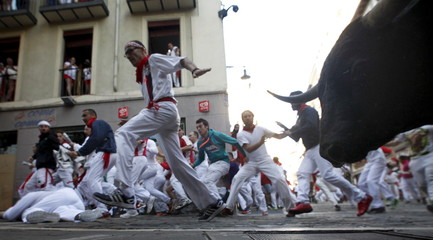 Runners sprint alongside a Garcigrande fighting bull at the Mercaderes curve during the seventh running of the bulls of the San Fermin festival in Pamplona