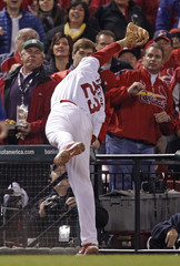 St. Louis Cardinals third baseman Freese leans into the stands to catch a foul ball hit by Texas Rangers' Hamilton during the fifth inning in Game 7 of MLB's World Series baseball championship in St. Louis