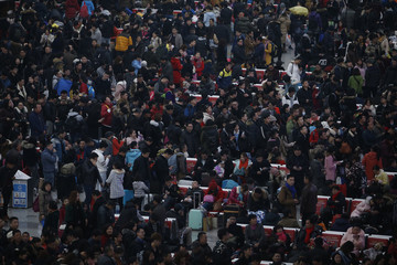 Passengers wait to board a train at Shanghai Hongqiao Railway Station during the travel rush ahead of the upcoming Spring Festival, in Shanghai