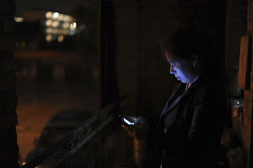 A mother looks at her phone as she stands on a balcony to wait for her child to return home in Hefei