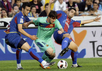 Barcelona's Messi  is challenged by Levante's Iborra and  Nadal during their Spanish first division soccer match in Valencia