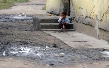 Roma baby squats on a step in a slum in Tiszavasvari