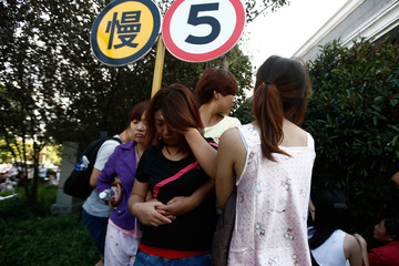 Female workers, who survived the ammonia leak, of a refrigeration unit of Shanghai Weng's Cold Storage Industrial Co. Ltd. are seen outside the factory in Shanghai
