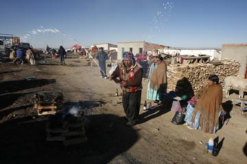 "Bolivian Aymara witchdoctor sprays beer next offerings to ""Pachamama"" in La Apacheta"