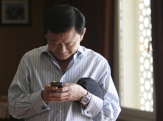 Thailand's former prime minister Thaksin Shinawatra checks one of his mobile phones during a meeting near his home in Dubai