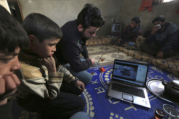 Naser, a 12-year-old boy, sits with Free Syrian Army fighters as they watch a video clip on a computer at a safehouse in Maarshmarein village, in the countryside of Maaret al-Naaman, in Idlib