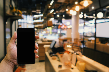 man holding smartphone with blank screen in the front of blurred restaurant background for reserve online; payment; coworking space conceptual.