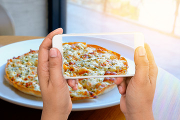 People using smart phone taken a pizza photo and with sunlight background for conceptual online service; share; delivery