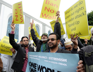 People hold protest signs after attending Friday prayers at the Islamic Center of Southern California in Los Angeles