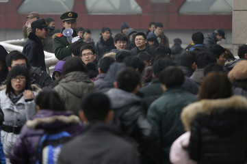 A paramilitary police officer keeps order as passengers crowd at an entrance of the Beijing West Railway Station