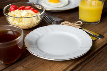 Breakfast table served with corn porridge, fried egg and juice