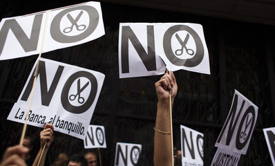 Civil servants hold banners during a protest against government austerity measures in front of the Treasury and Public Administration Ministry in Madrid