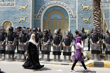 Women walk past riot police as they stand guard during a protest by Jordanian lawyers in front of the Iraqi embassy in Amman