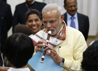 India's PM Modi tries to play soprano recorder before school children at music class at Taimei Elementary School in Tokyo