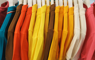 multi color t-shirts hanging on hangers.