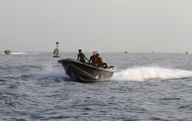 Iranian smugglers ride on a boat near the port of Khassab in Oman