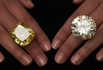 A model poses with a vivid yellow 100.09 carats diamond and a 103.46 carats diamond ring during an auction preview at Sotheby's in Geneva