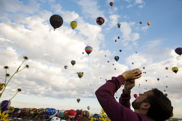 A man uses his phone to take pictures as hundreds of hot air balloons lift off on the first day of the 2015 Albuquerque International Balloon Fiesta in Albuquerque, New Mexico