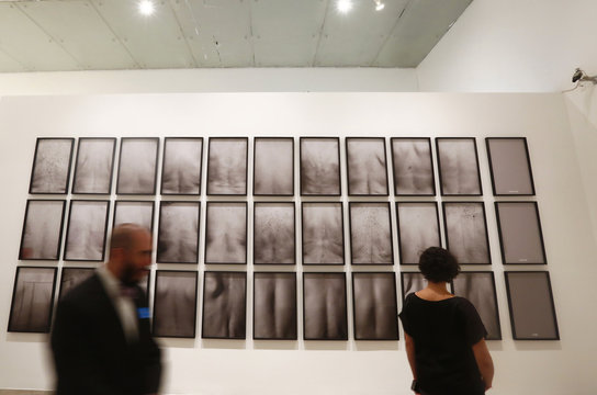 Visitors walk in front of pictures showing backsides of people from the various social backgrounds at University Museum of Contemporary Art in Mexico City