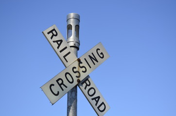 Railroad crossing sign and a clear blue sky