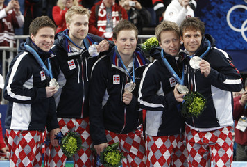 Norway's curling team celebrate with their silver medals after their men's gold medal curling game against Canada