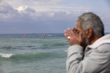 Lebanese man prays as marine diver teams in boats search for the Ethiopian Airlines plane which crashed into the Mediterranean sea, at Naameh area, south of Beirut
