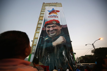Supporters of Venezuela's late president Hugo Chavez look up at his image on a banner on a building, during the first anniversary of his death in Caracas