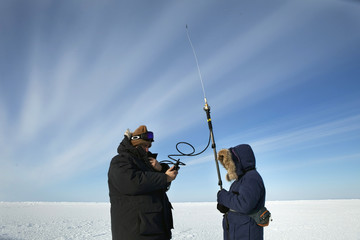 Workers use a radio to verify their position after delivering supplies to a remote warming station near the 2011 Applied Physics Laboratory Ice Station north of Prudhoe Bay