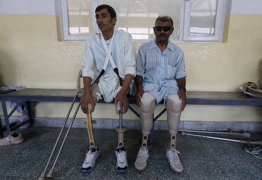 Mohammad Zaman and Abdul Basir sit at an ICRC hospital for war victims at the Orthopedic Center of the International Committee of the Red Cross in Kabul