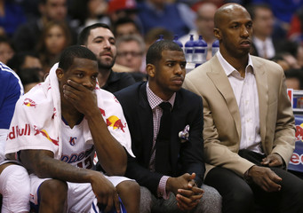 Los Angeles Clippers injured guard Paul and teammates Billups and Bledsoe watch their team lose to the Oklahoma City Thunder during their NBA basketball game in Los Angeles