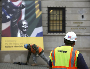 Construction workers look at a sign celebrating the life of Nelson Mandela outside of the South African Embassy in Washington