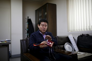Seo Jae-pyoung, the secretary general of the association of the North Korean defectors, looks at a Workers' Party membership card holder while demonstrating the use of it during an interview with Reuters in Seoul