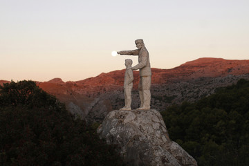 A view of a monument dedicated to forest rangers as the supermoon sets over the horizon at dawn at nature park and biosphere reserve near Malaga