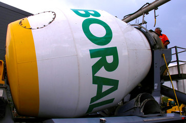 A worker keeps watch as he loads a cement truck adorned with the logo of Boral Ltd in Sydney, Australia