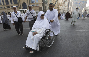 A Muslim man pushes his mother as she is seated in a wheelchair after performing Friday prayers at the Grand mosque during the annual haj pilgrimage in the holy city of Mecca