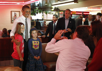 U.S. President Barack Obama poses for a picture with girls at Roscoe's in Los Angeles