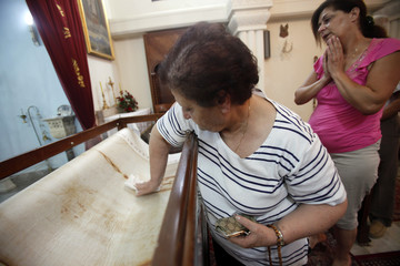 A woman touches the surface of a copy of the original Shroud of Turin displayed at an Armenian Catholic Church in Beirut
