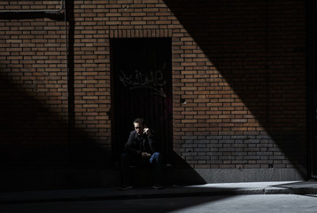 A man sitting on a doorstep talks on a mobile phone in central Madrid