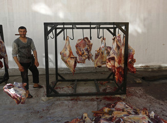 An Afghan butcher throws a piece of beef on the first day of Eid al-Adha in Kabul