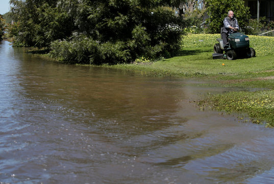A man mows his front lawn as floodwaters lap at his home following heavy rains in the midwestern New South Wales town of Forbes