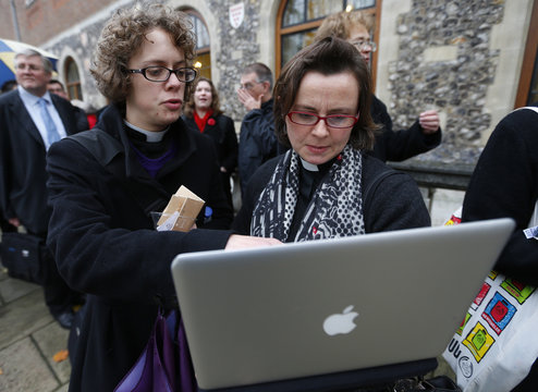 Female members of the clergy look at a laptop as they queue for a seat in the public gallery outside Church House where the Church of England Synod is meeting to vote on the ordination of women bishops, in central London