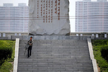 A man carries a bicycle down the stairs in central Pyongyang