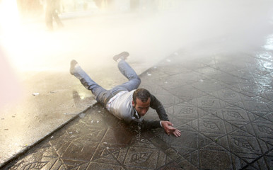 An anti-government protester falls as the police disperse the crowd with water cannons during a protest in Ankara