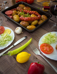 Res roasted potatoes with sausages in a pan. Served with mixed vegetables and wine