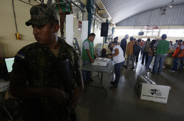 A soldier keeps watch as workers of the Supreme Electoral Tribunal scan boxes with ballots used in Sunday's general elections in Tegucigalpa