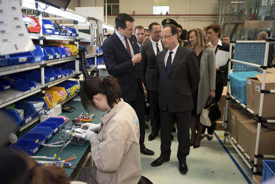 France's President Hollande tours a workshop of Bernard Controls, a French business which manufactures electric actuators and controls for the automation of industrial valves and dampers, during a visit to Beijing