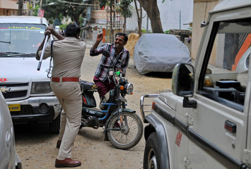 Police raises his baton at a man who defied a curfew in Bengaluru, following violent protests after India's Supreme Court ordered Karnataka state to release water from the Cauvery river to the neighbouring state of Tamil Nadu