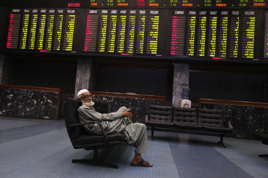 A man sits on a couch underneath an electronic board displaying share prices during a trading session at the Karachi Stock Exchange